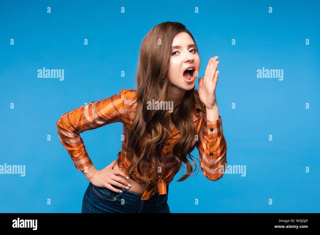 Schöne junge Frau in legere Kleidung laut schreien. Stockbild