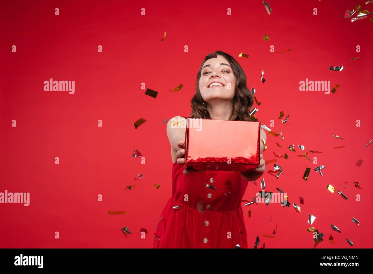 Wunderschöne brünette Mädchen im roten Kleid in Konfetti. Stockbild