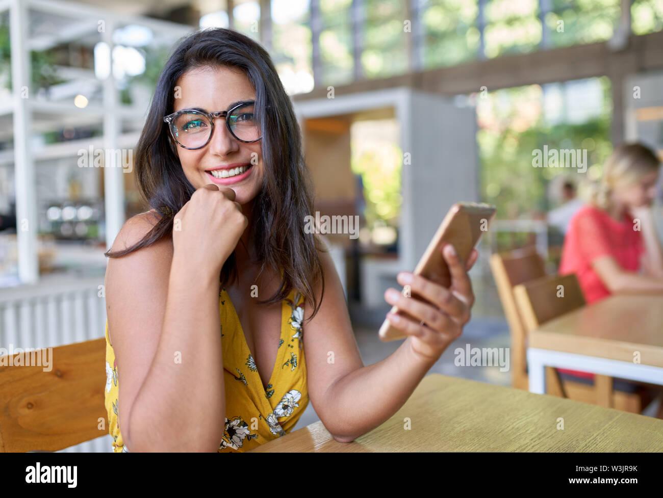Candid lifestyle Portrait von Lachen hispanic Tausendjährigen student Eingabe über Handy in schickes, modernes und helles Café mit Pflanzen Stockbild