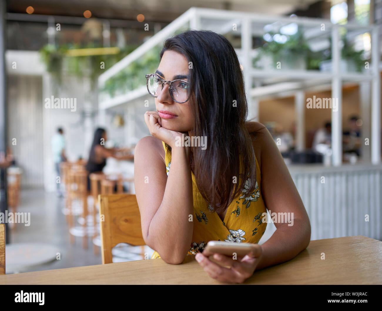 Candid lifestyle Portrait von schönen Hispanic tausendjährigen Frau Blick aus Fenster holding Handy in modernen trendigen und helle Café mit Stockbild
