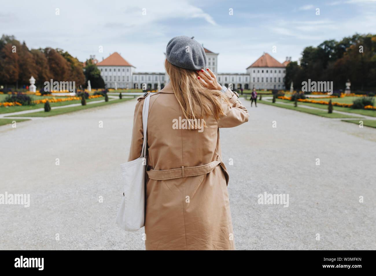Frau mit Mantel und Baskenmütze durch Schloss Nymphenburg in München, Deutschland Stockfoto