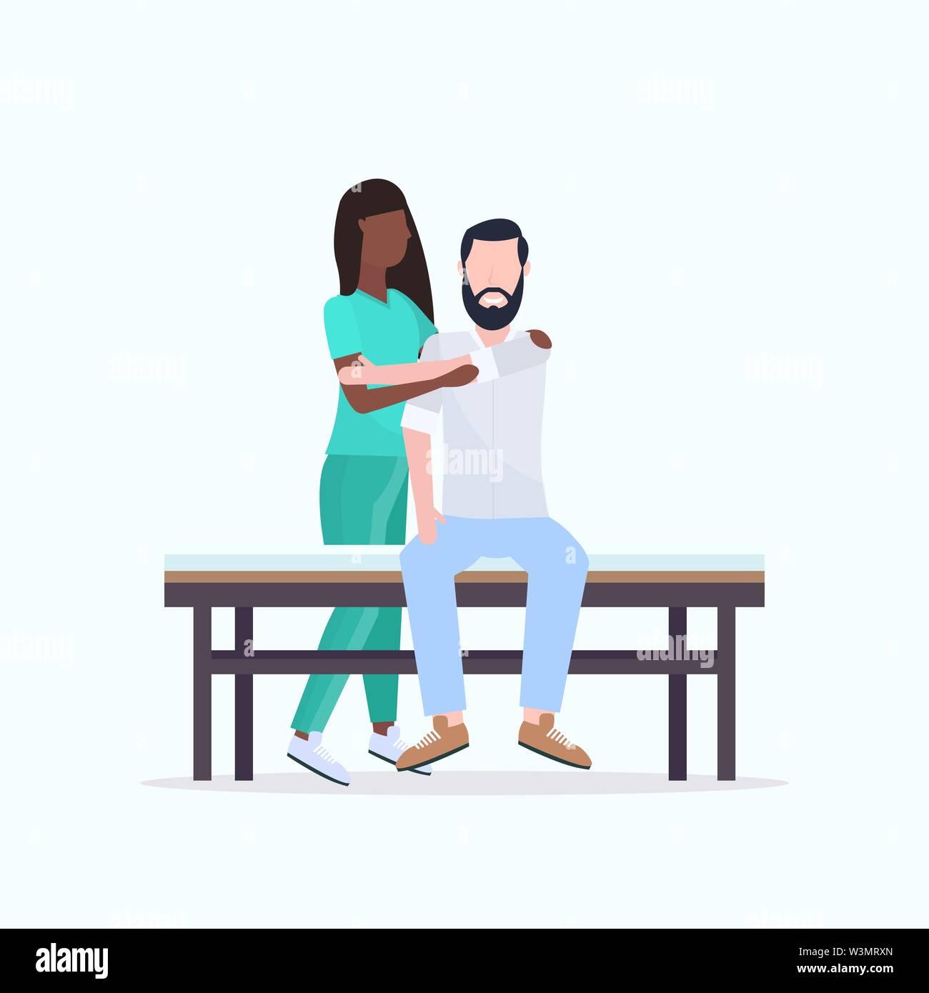 Junge Mann sitzt auf dem Bett afrikanische amerikanische Masseurin Therapeuten in Uniform tun Heilung Massage Körper des Patienten Manuelle Therapie Physiotherapie co Stockbild