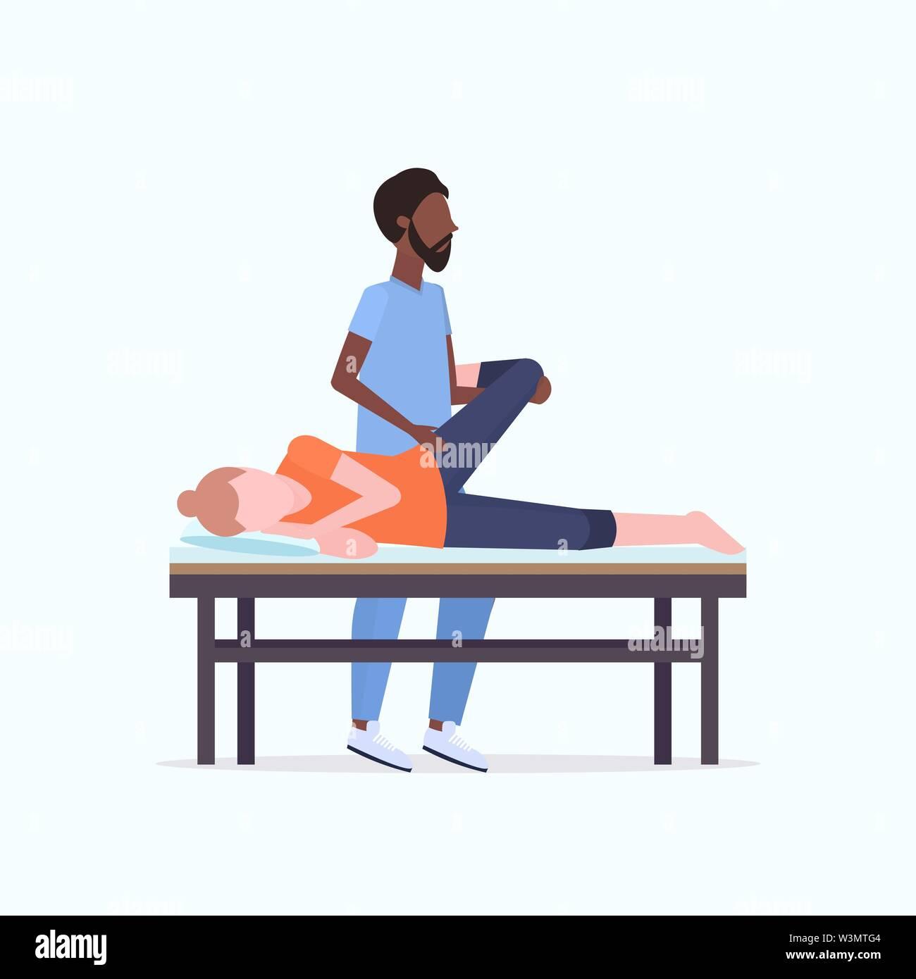 Junge Mädchen liegt auf Massage bed african american Masseur, Therapeut, heilende Behandlung massiert behandelnden Beine Handbuch sport Physikalische thera Stockbild