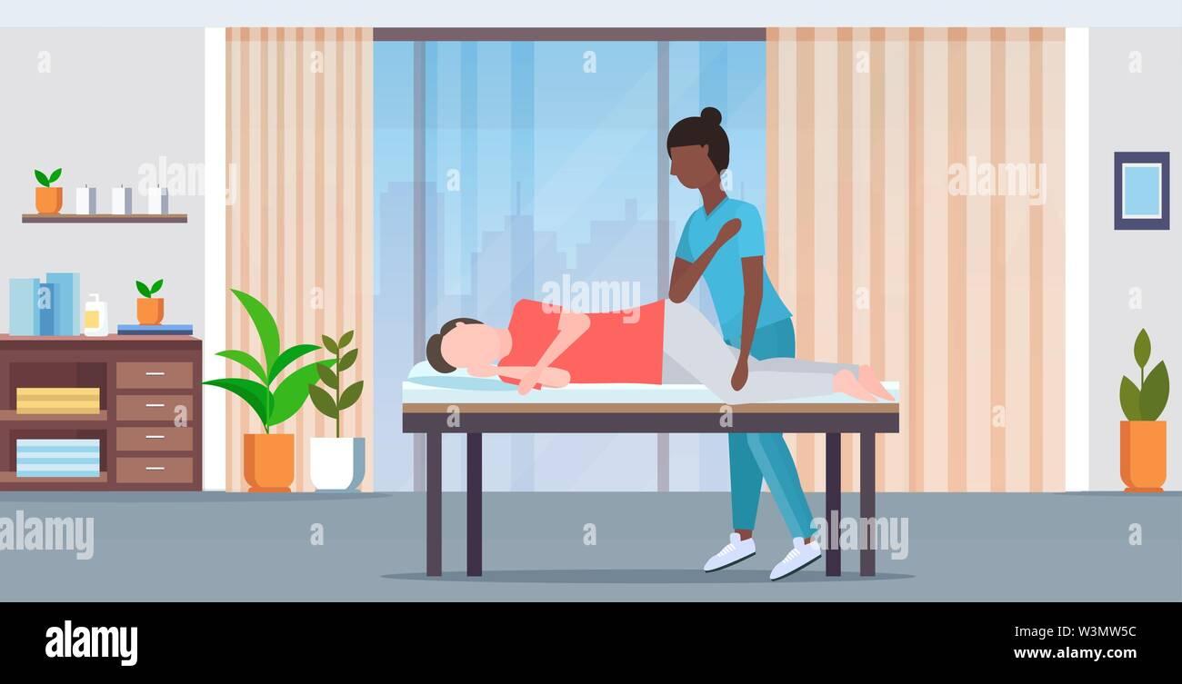 Mann liegen auf Massage bed afrikanische amerikanische Masseurin Therapeut tun Heilung massieren verletzte Patienten manuelle physikalische Therapie Konzept moderne Stockbild