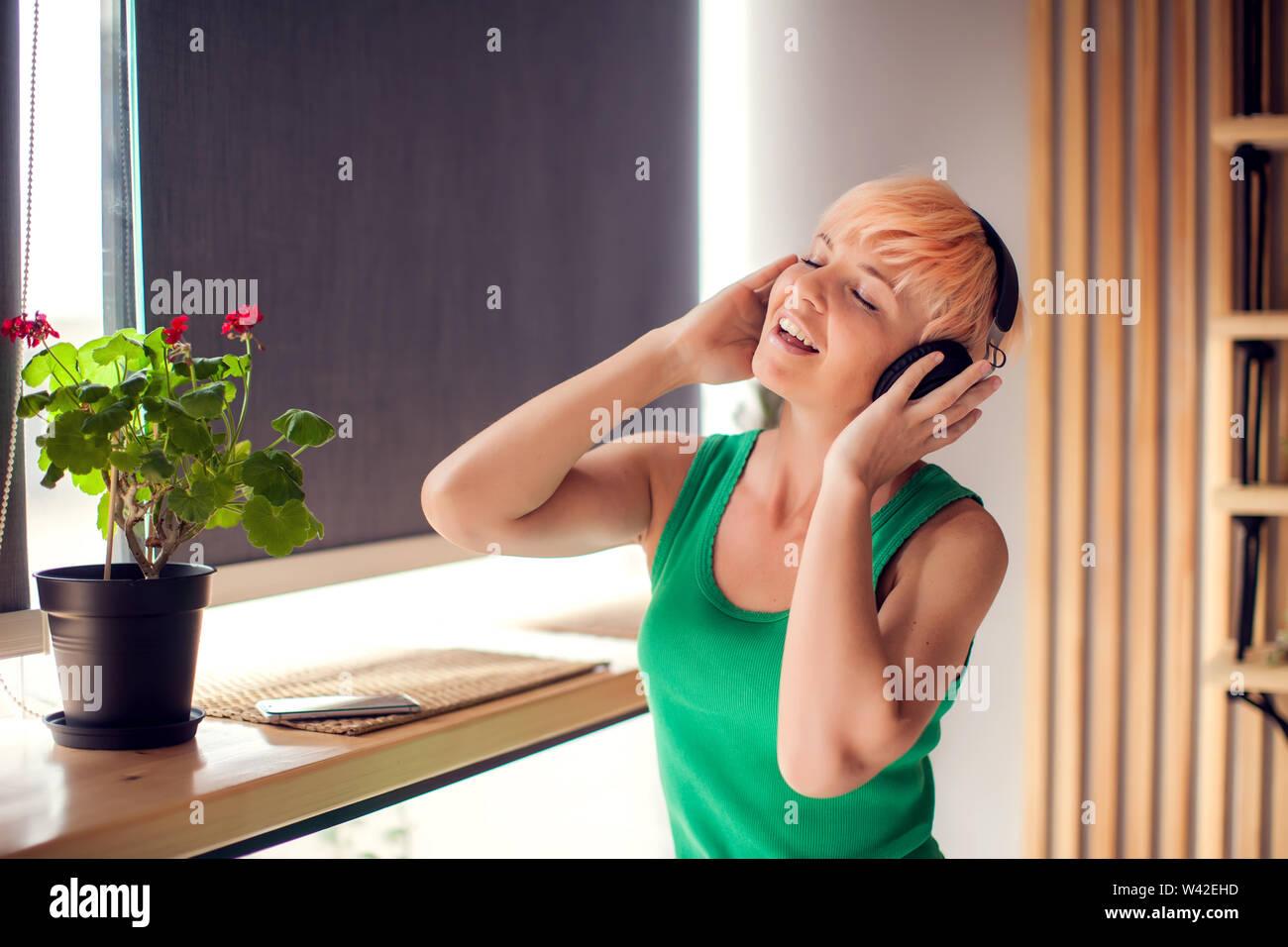 Junge Frau mit kurzen Haaren für Musik hören mit Kopfhörern indoor. Menschen und Lifestyle Konzept Stockfoto