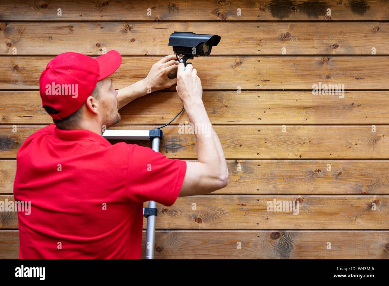 Home security-mann Installation außen Überwachungskamera auf Holz wand Platz kopieren Stockfoto