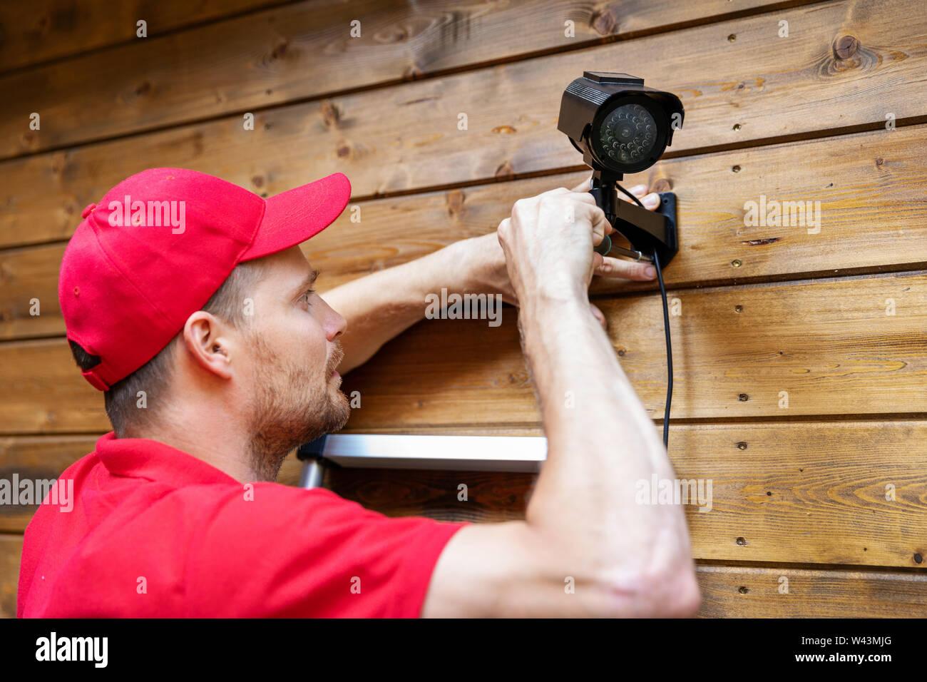 Security System Technician Installation von Überwachungskameras auf hölzernen Haus Wand Stockfoto