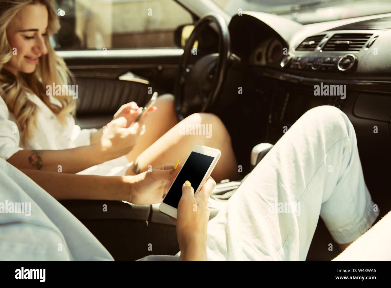 Die jungen lesbischen Paar Vorbereitungen für die Urlaubsreise auf dem Auto in sonniger Tag. Frauen sitzen und auf das Meer, den Fluss oder Meer zu gehen. Konzept der Beziehung, Liebe, Sommer, Wochenende, Hochzeitsreise. Stockfoto