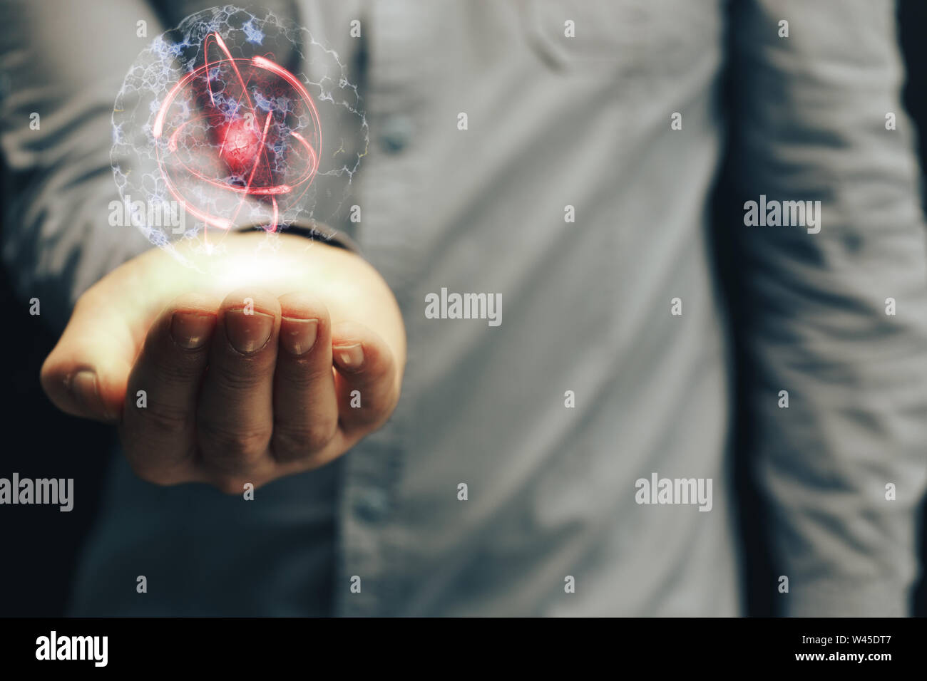 Die menschliche Hand, die eine Zelle teilen und Atom. Nebel Staub. Mixed Media. Stockfoto