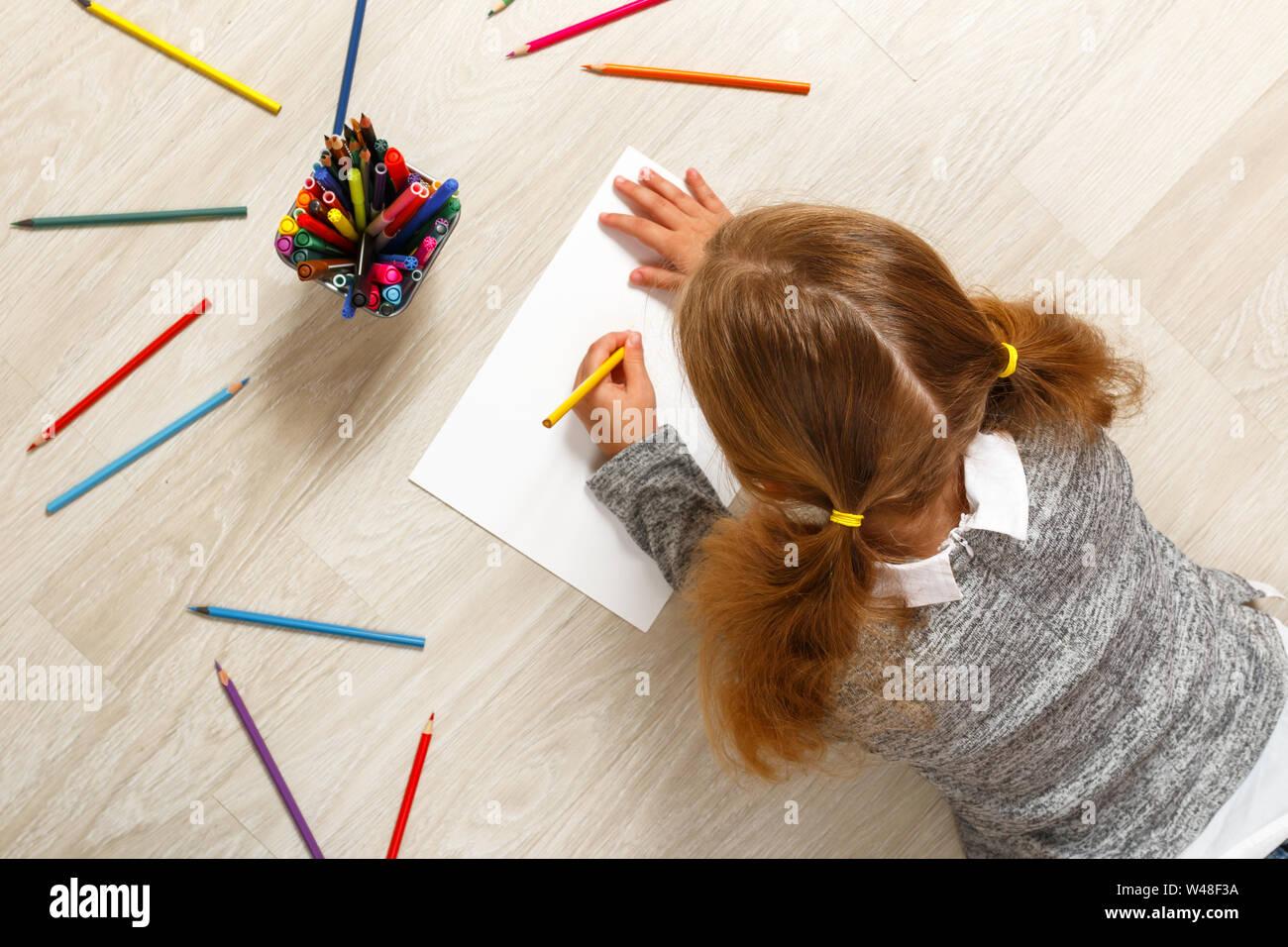 Blick von oben auf ein kleines Mädchen Lügen und Malerei auf dem Boden in ihrem Zimmer zu Hause. Stockfoto