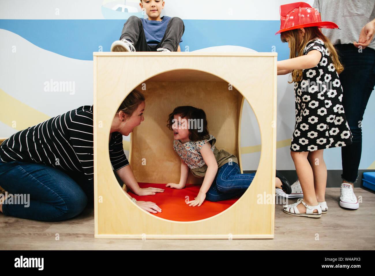 Mädchen in einem Cube spielen Struktur lächelt sie an Lehrer Stockfoto