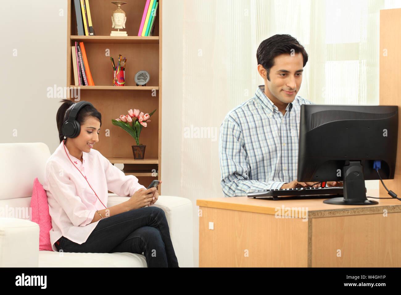 Indischen Mann arbeitet auf einem Desktop-pc mit seiner Frau anhören von Musik auf dem Handy Stockfoto