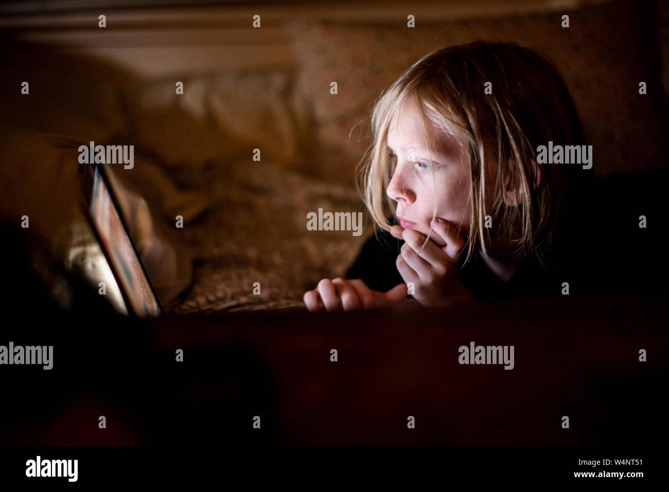 Kind auf dem Bildschirm in der Dunkelheit Stockfoto