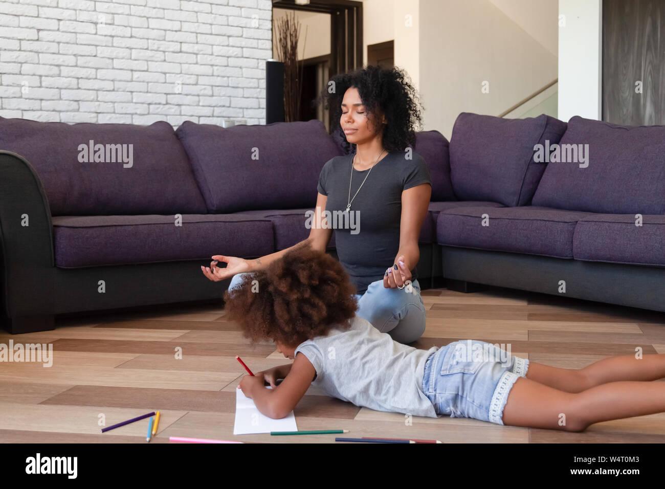 Afrikanische Mutter Yoga, während ihre Tochter Zeichnung auf dem Boden Stockfoto