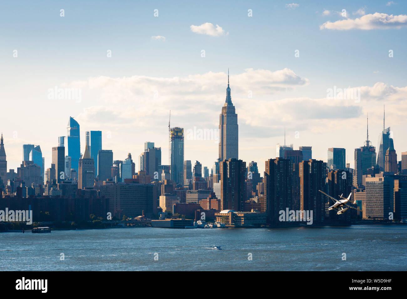 USA Stadt, mit Blick auf die Manhattan Skyline und Waterfront mit einem Wasserflugzeug absteigend zum East River, New York City, USA. Stockfoto
