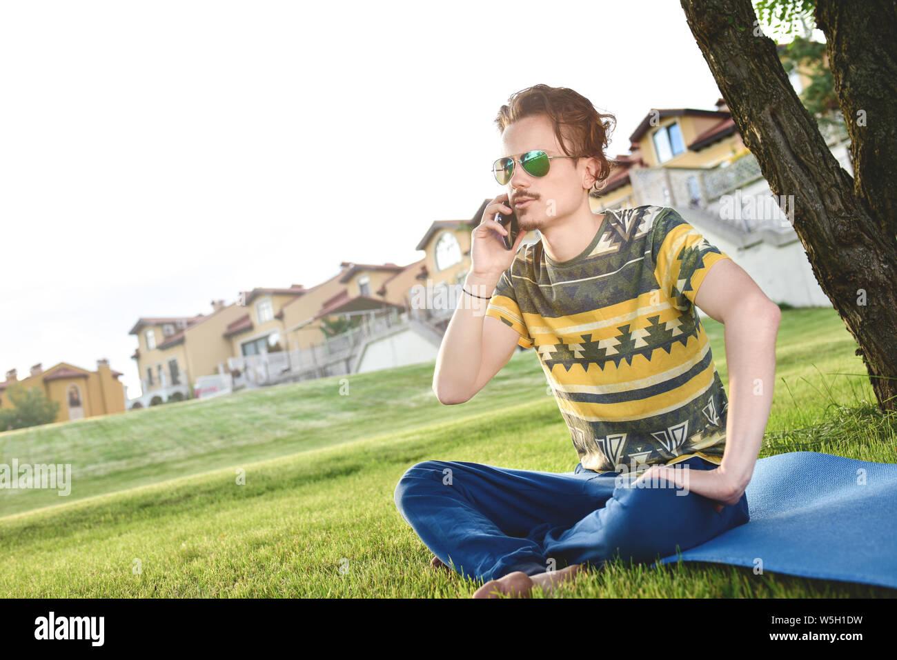 Junge stilvolle hübscher Kerl sitzt auf Gras und Telefonieren im Park ausruhen. Pause Stockfoto