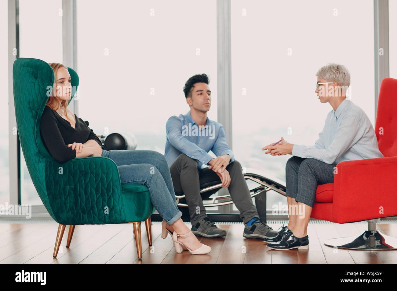 Junger Mann und Frau sind chatten, während in einem Stuhl sitzen. Brainstorming Konzept. Stockfoto
