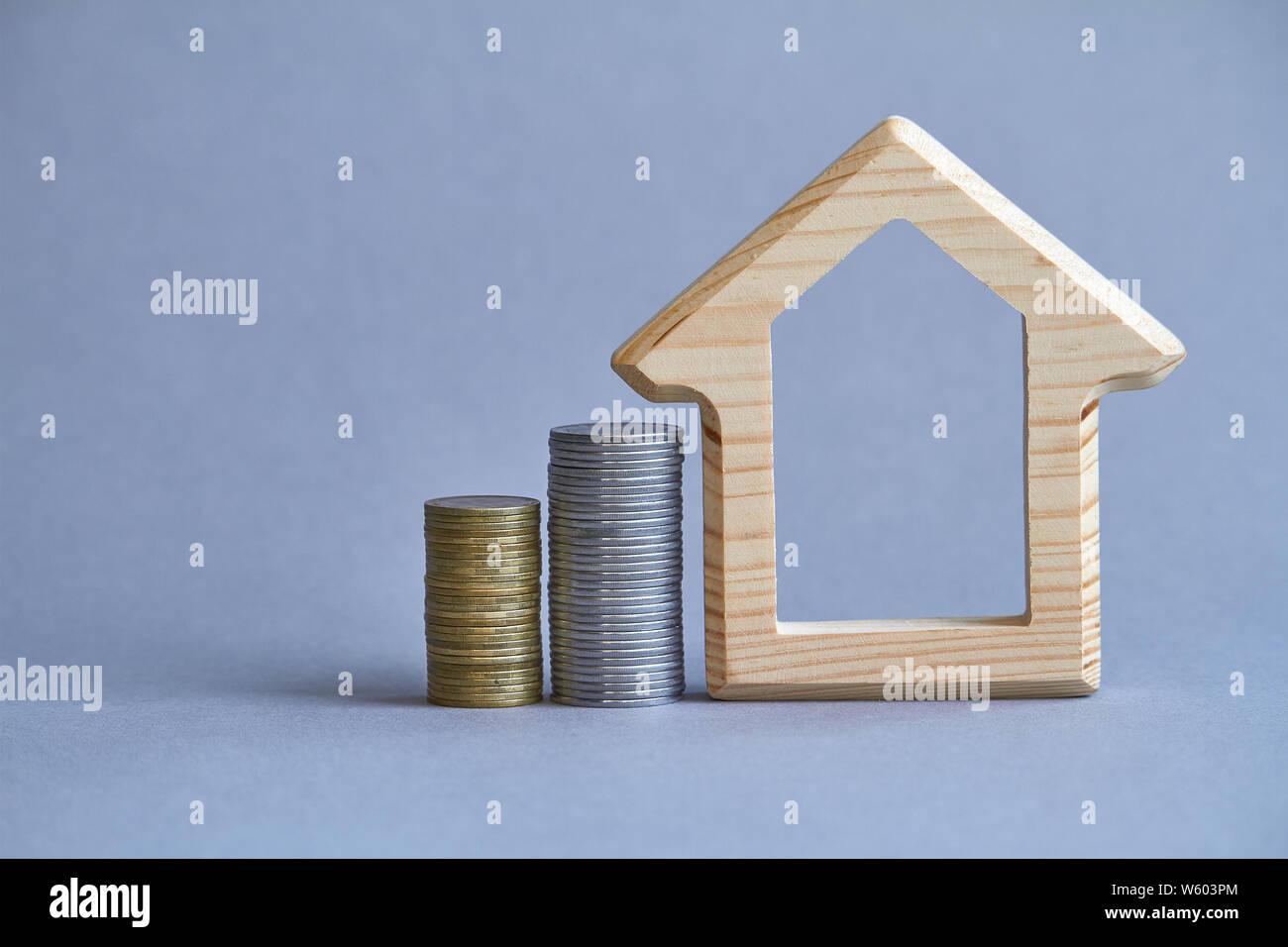 Holz- Figur von Haus mit zwei Spalten von Münzen in der Nähe auf grauem Hintergrund, das Konzept der Kauf oder die Vermietung eines Gebäudes, selektiver Fokus Stockfoto
