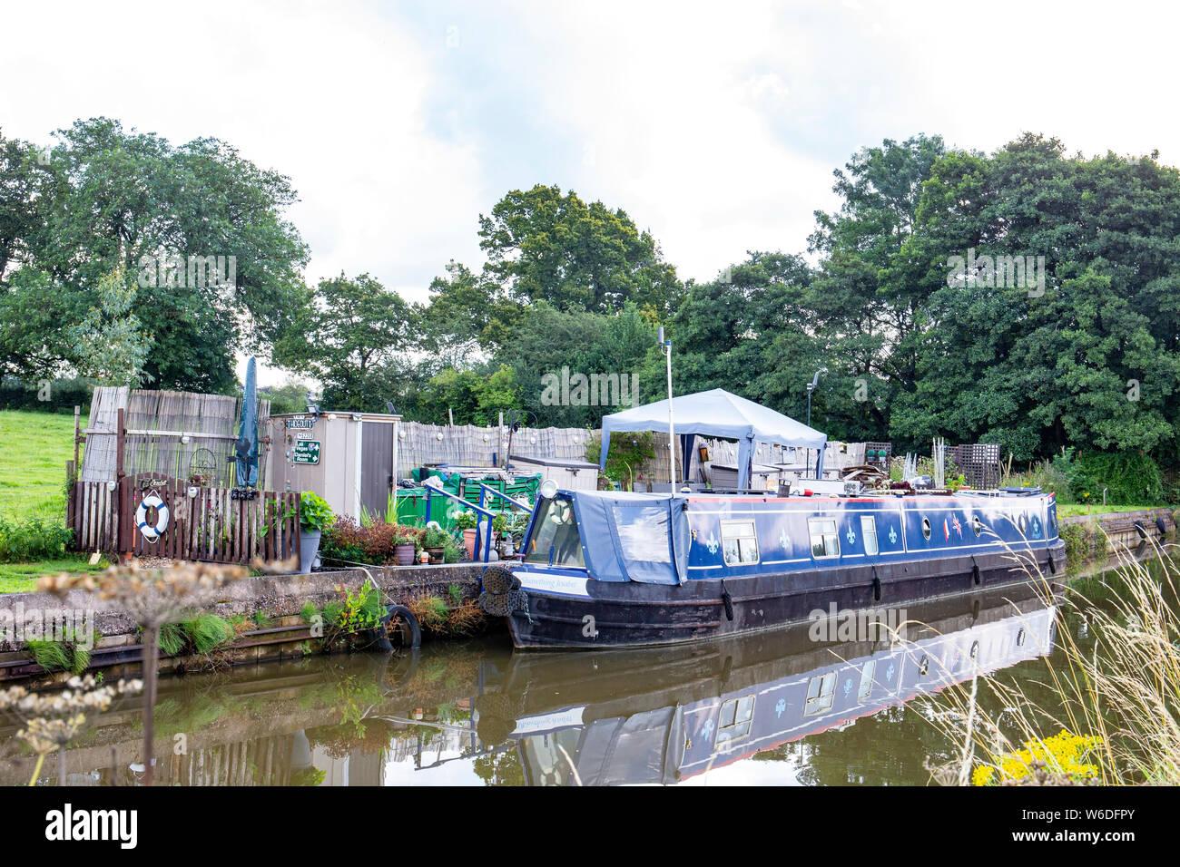 Schmale Boot namens Shawthing Jesabel mit eigenem Garten festgemacht, und Messe, auf der Trent und Mersey Canal in Cheshire UK Stockfoto