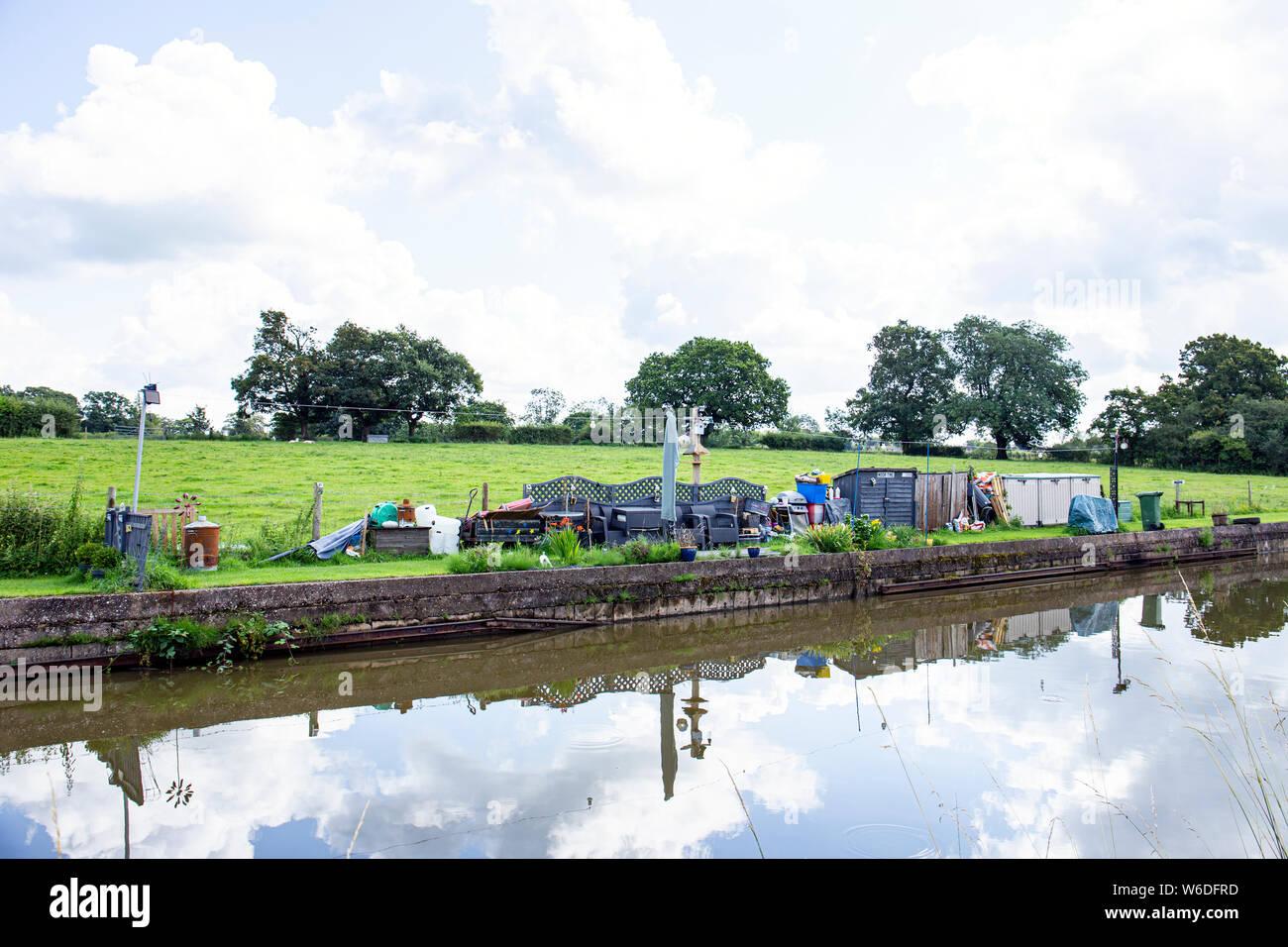 Reservierter Liegeplatz Platz für einen schmalen Boot genannt Moor Zeit mit eigenem Garten, und Messe, auf der Trent und Mersey Canal in Cheshire UK Stockfoto