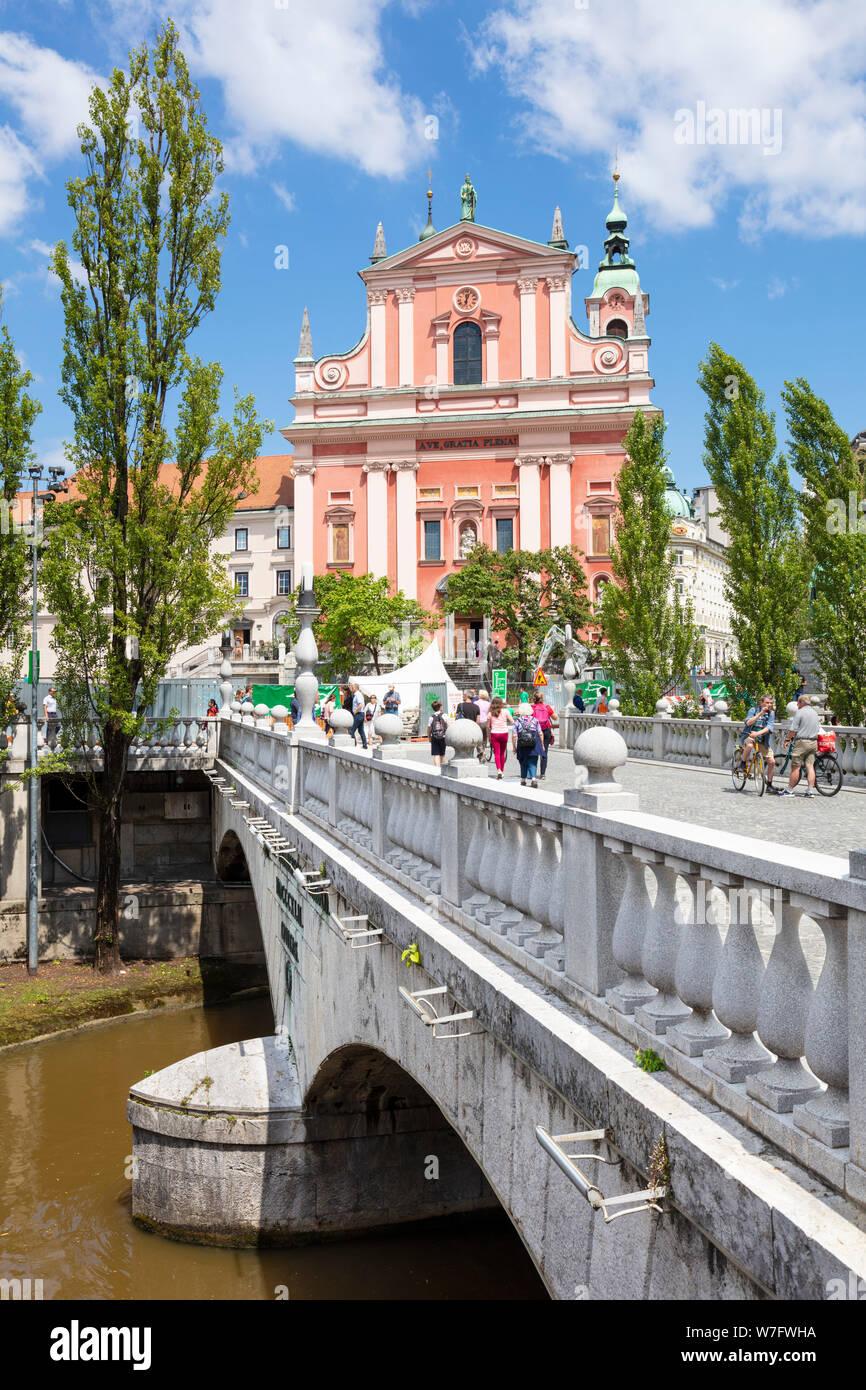 Die Rosa Franziskanerkirche in Prešerenplatz und Touristen zu Fuß über die drei Brücken über den Fluss Ljubljanica ljubljana Slowenien EU Europa Stockfoto