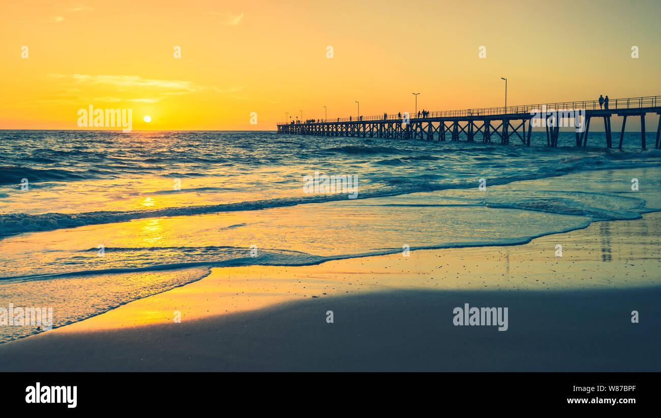 Port Noarlunga Bootsanleger mit Fischer bei Sonnenuntergang viwed von Strand, South Australia Stockfoto