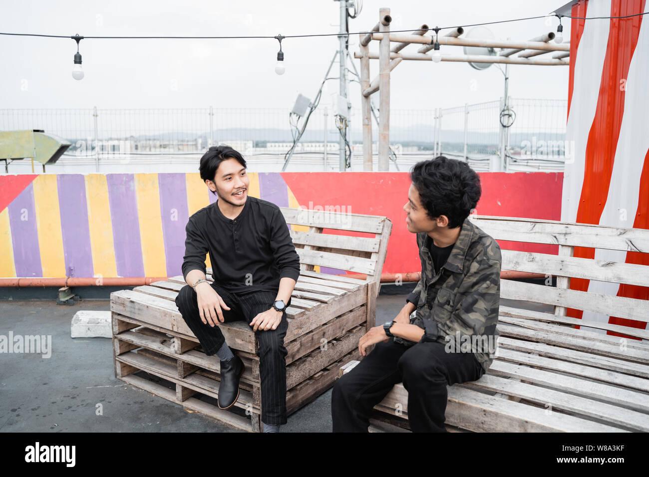 Zwei junge Mann sitzt auf dem Holzbrett Stockfoto