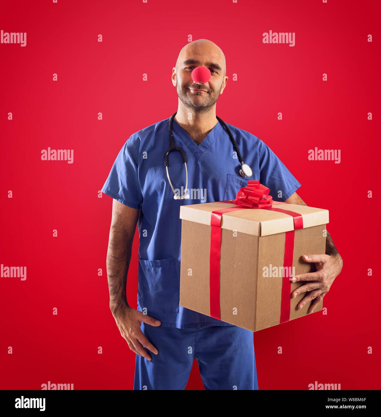 Krankenschwester mit clown Nase und Geschenk auf rotem Hintergrund Stockfoto