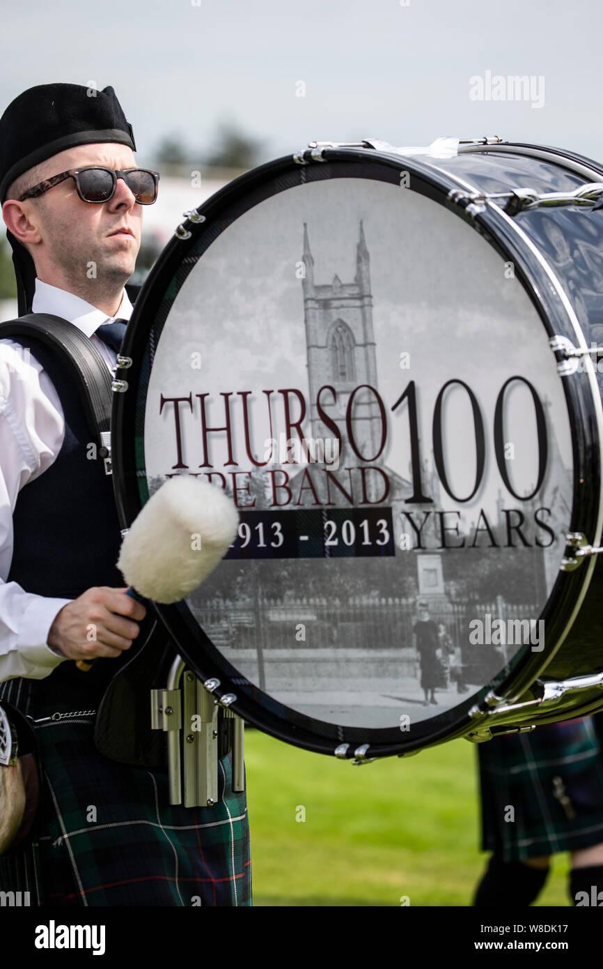 Bass Drummer in Thurso Pipe Band spielen an der Halkirk Highland Games in Caithness, Schottland Stockfoto