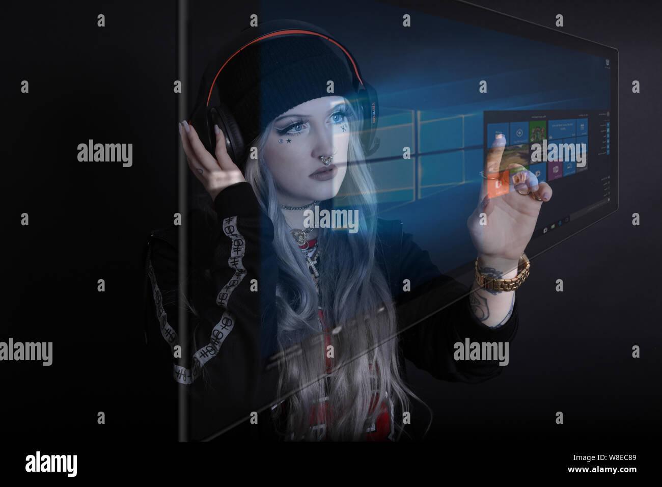Moderne Millennial Interaktion mit Technologie, Microsoft Surface, trägt Kopfhörer, mit Handgesten mit Virtual Reality-Bildschirm AI interagieren Stockfoto