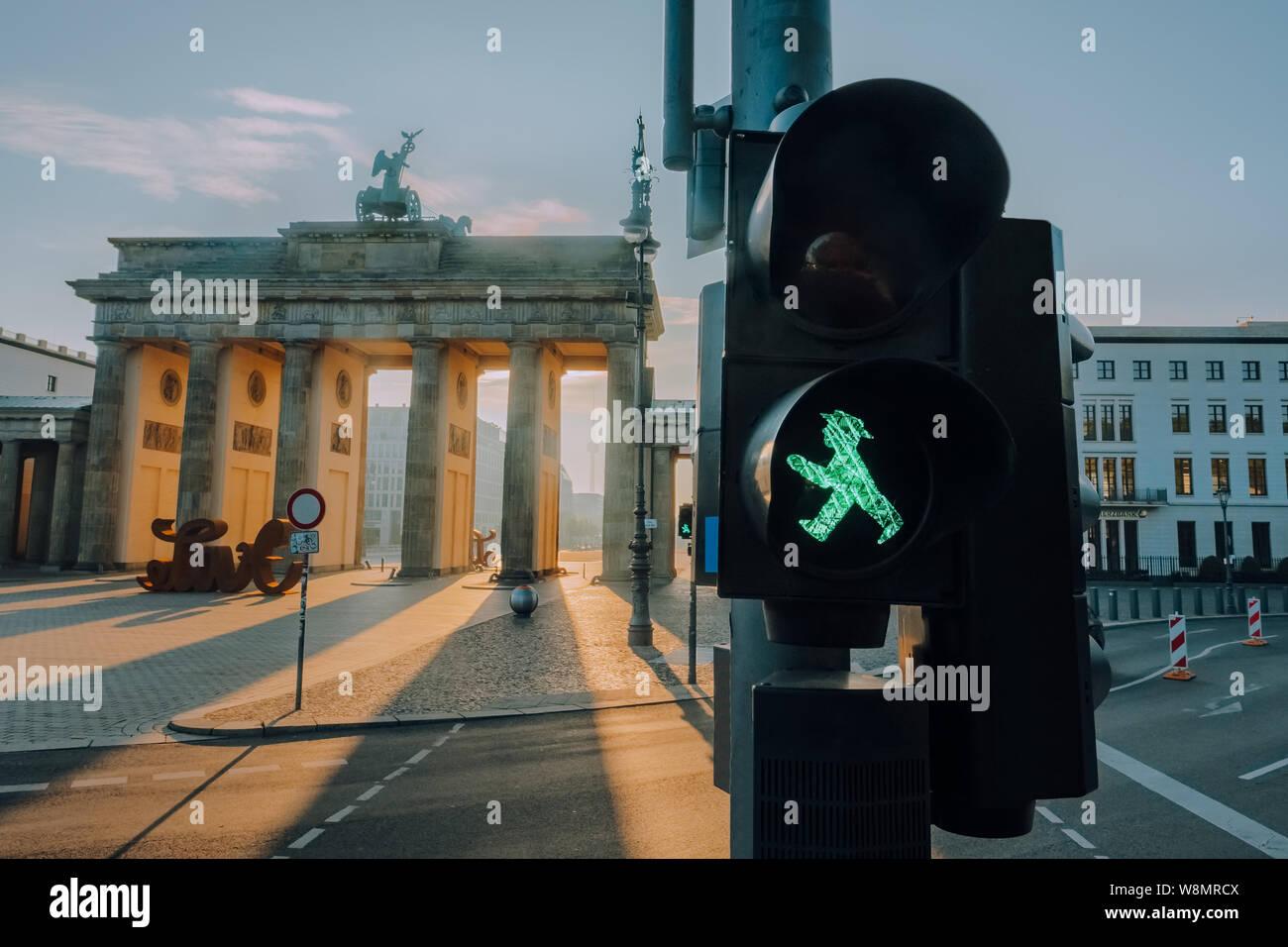 Ampelmann Berlin grüne Ampel close-up mit Brandenburger Tor im Hintergrund bei Sonnenaufgang Stockfoto
