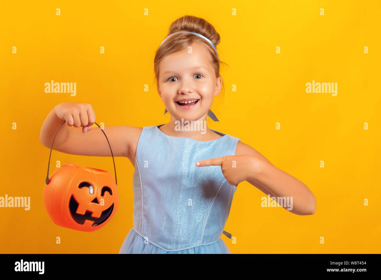 Halloween Party. Kleines Mädchen gekleidet, wie Aschenputtel auf gelbem Hintergrund. Das Kind hält einen Eimer von Jack Lantern und zeigt mit dem Finger auf den Kürbis Stockfoto
