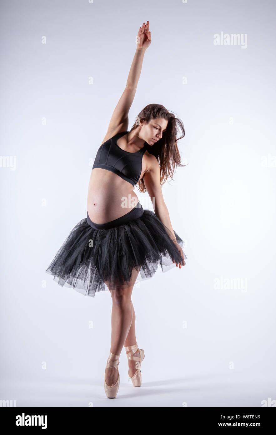 Junge schöne schwangere Ballerina mit schwarzen Kleid posiert im Studio. Stockfoto