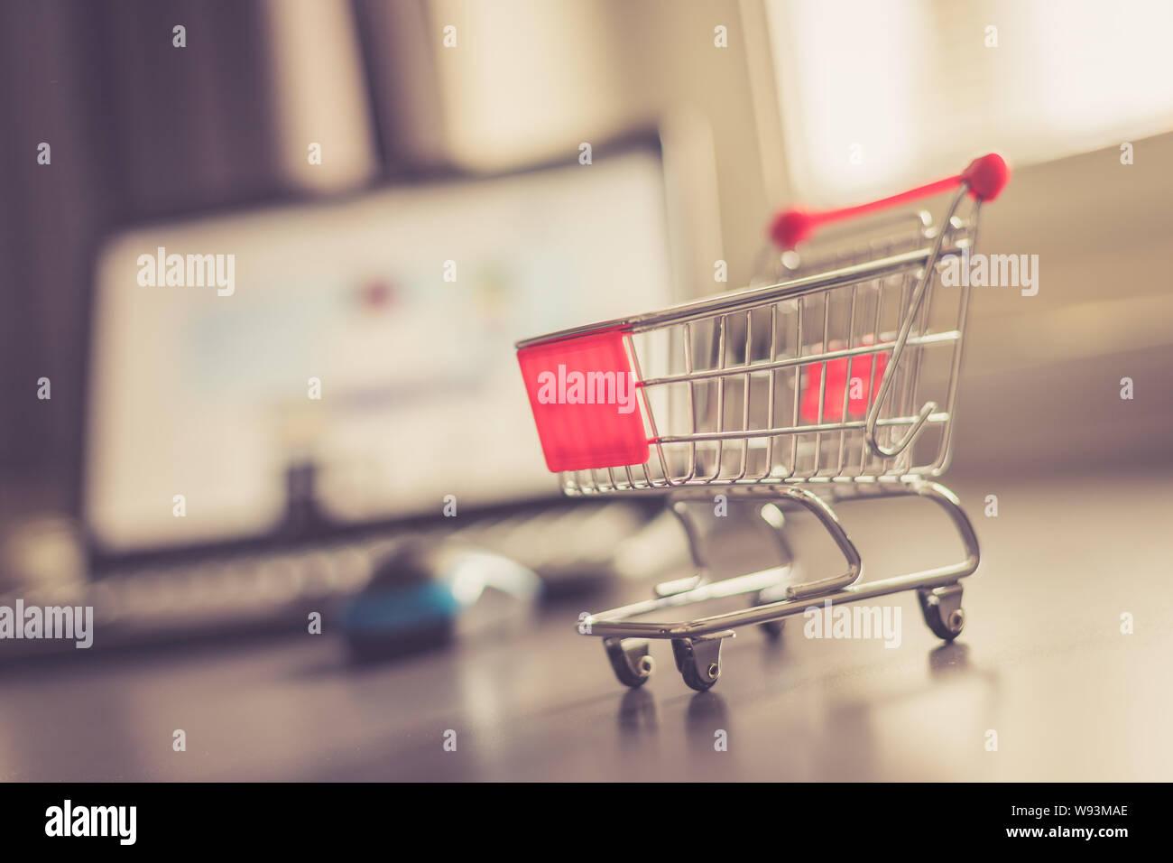 Online-Shopping Konzept: Miniatur Warenkorb, Laptop und Maus im verschwommenen Hintergrund Stockfoto