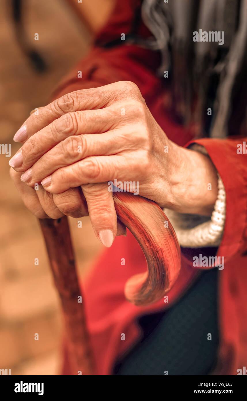 In der Nähe der Hände von einer alten Frau lehnte sich auf Zuckerrohr Stockfoto