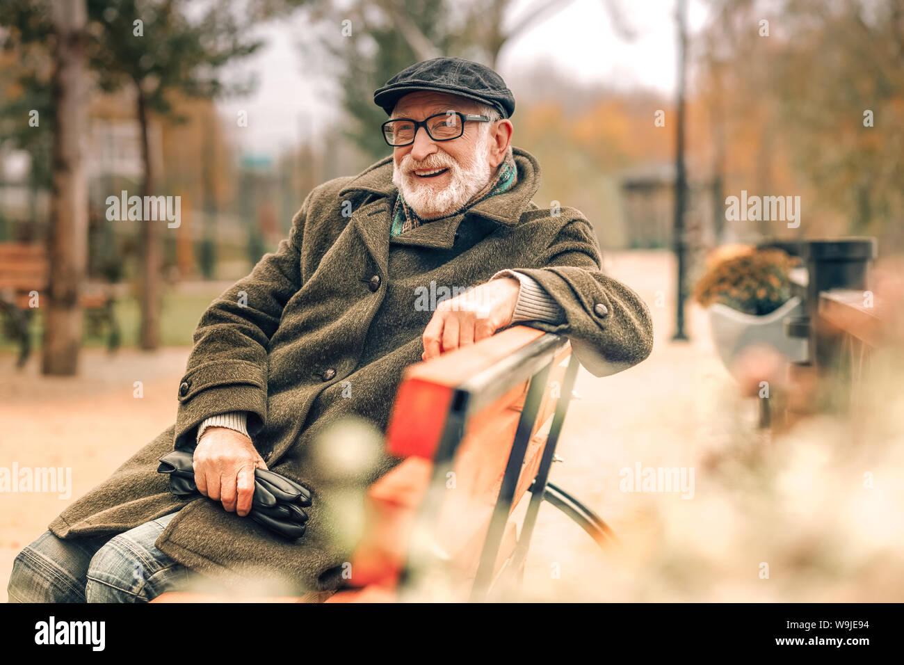 Elegante älterer Mann sitzt auf der Bank im Park Stockfoto