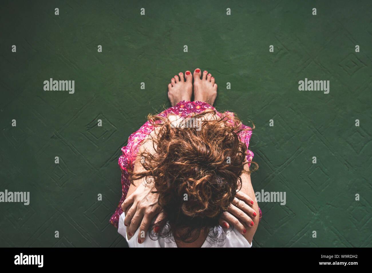 Blick von oben auf die trendige Mädchen sitzen auf Grün vintage Stock. Barfuß Frau mit roten Nägeln Arme gekreuzt. Stilvolle hippie Frau mit lockigem Haar meditieren in Stockfoto