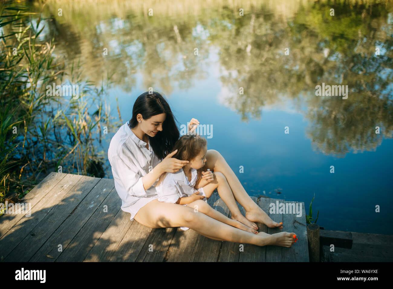 Mutter und Tochter sitzen auf einem hölzernen Brücke über einen Fluss mit Reflexion der Bäume und der Himmel im Wasser. Stockfoto