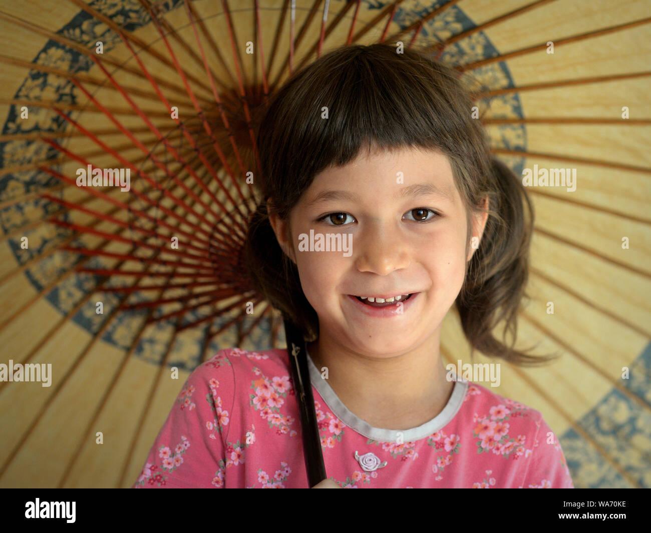 Cute Misch - laufen kleine Mädchen (Kaukasische und Südostasiatischen) Lächeln unter ihrer traditionellen chinesischen Öl- papier Sonnenschirm. Stockfoto