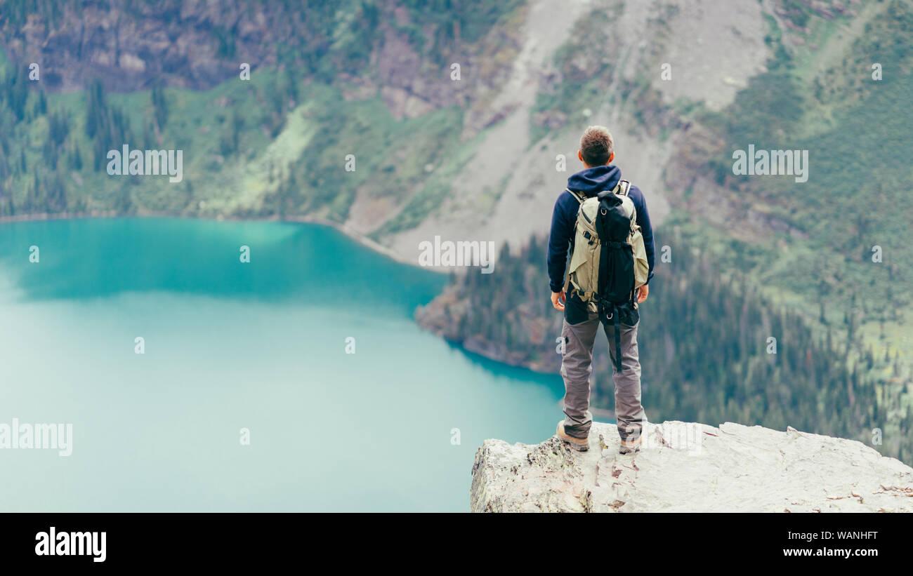 Männliche Wanderer steht auf einer Klippe am See im Glacier NP suchen Stockfoto