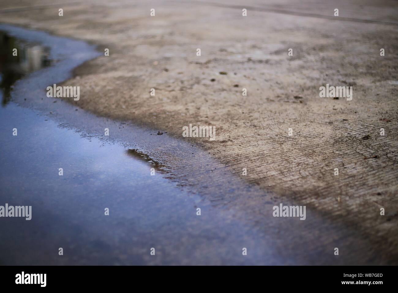 Konkrete Straße und Überschwemmung Wasser. schlechte Kanalisation Pfütze von Wasser überflutet regen Sturm auf der Straße Fläche links Stockfoto