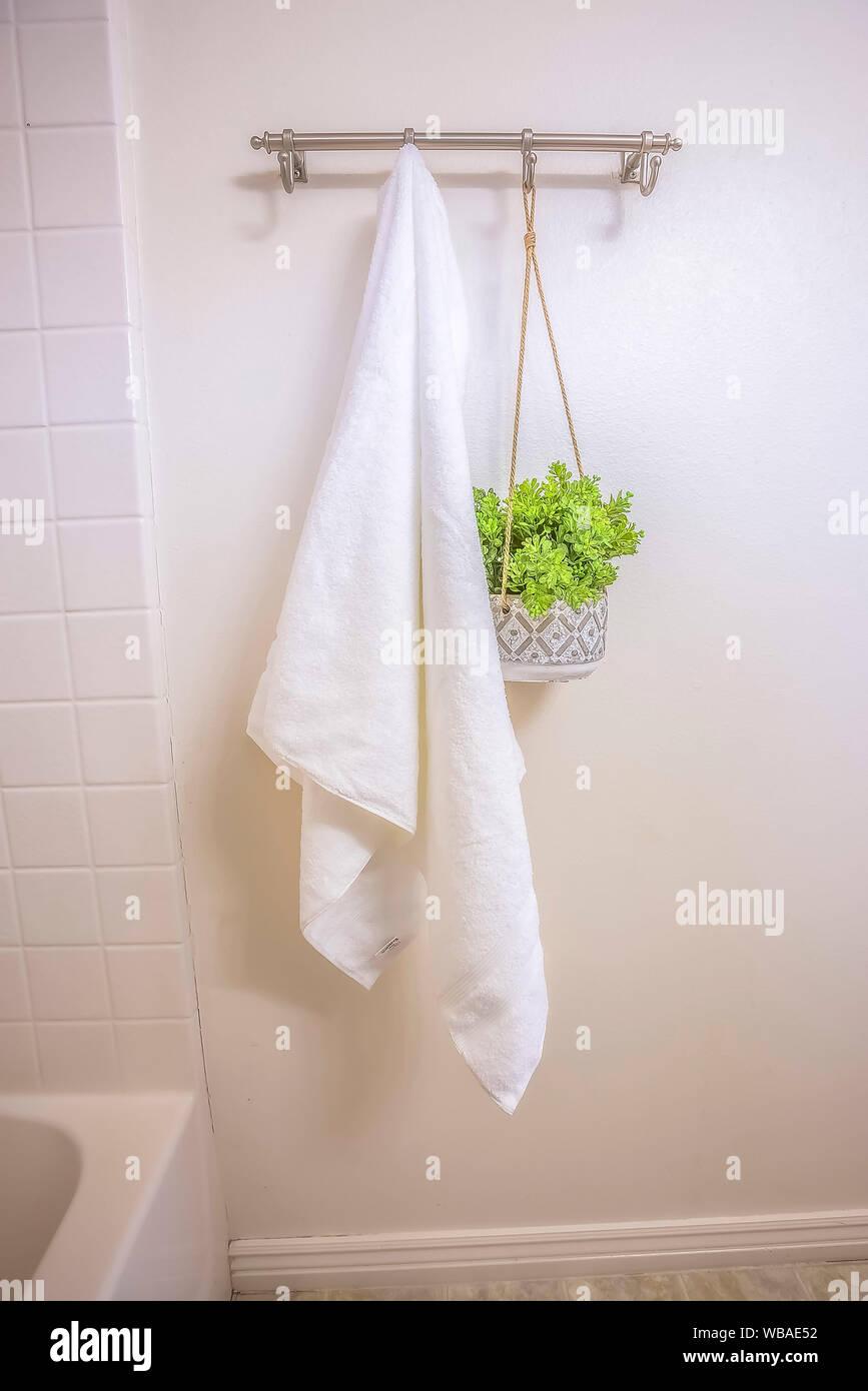 Weißes Handtuch und Zierpflanzen an der Wand aufhängen, Stab in ...