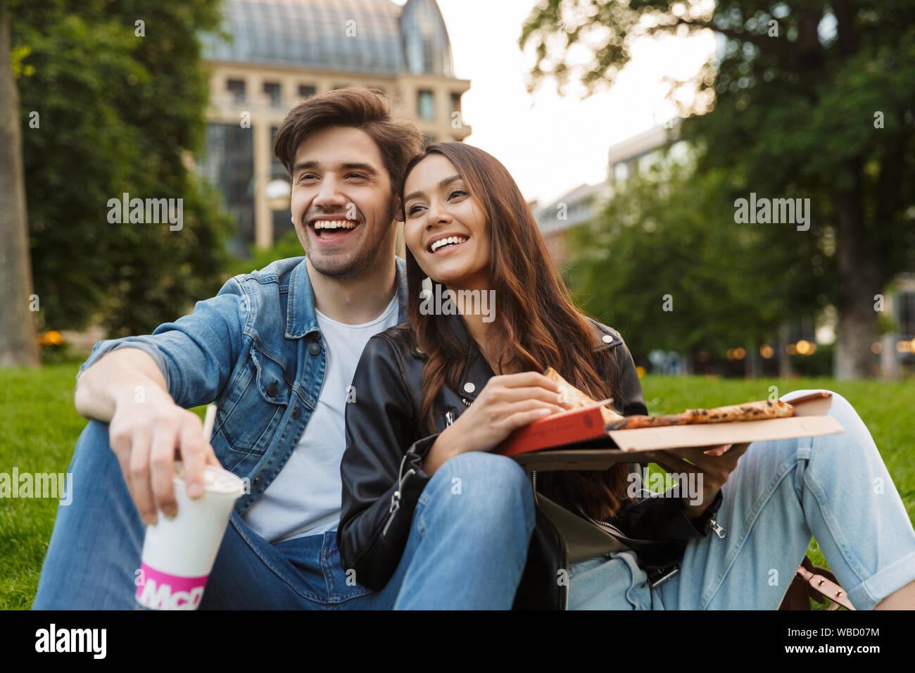 Foto von fröhlichen jungen Freunde Verliebten in der Natur sitzen Green Park im freien Pizza auf Picknick umarmen Essen. Stockfoto