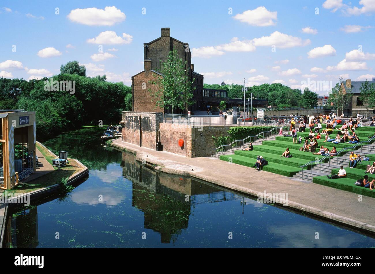 Leute sitzen auf Terrassen am Regents Kanal an der neu entwickelten Kohle Tropfen Hof, King's Cross, London UK Stockfoto