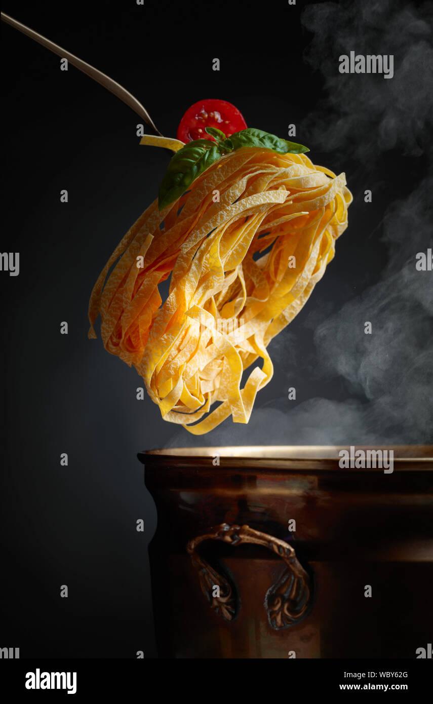 Hausgemachte rohes Ei Nudeln und altes Messing Topf mit heißem Wasser. Schwarzen Hintergrund. Kopieren Sie Platz. Stockfoto