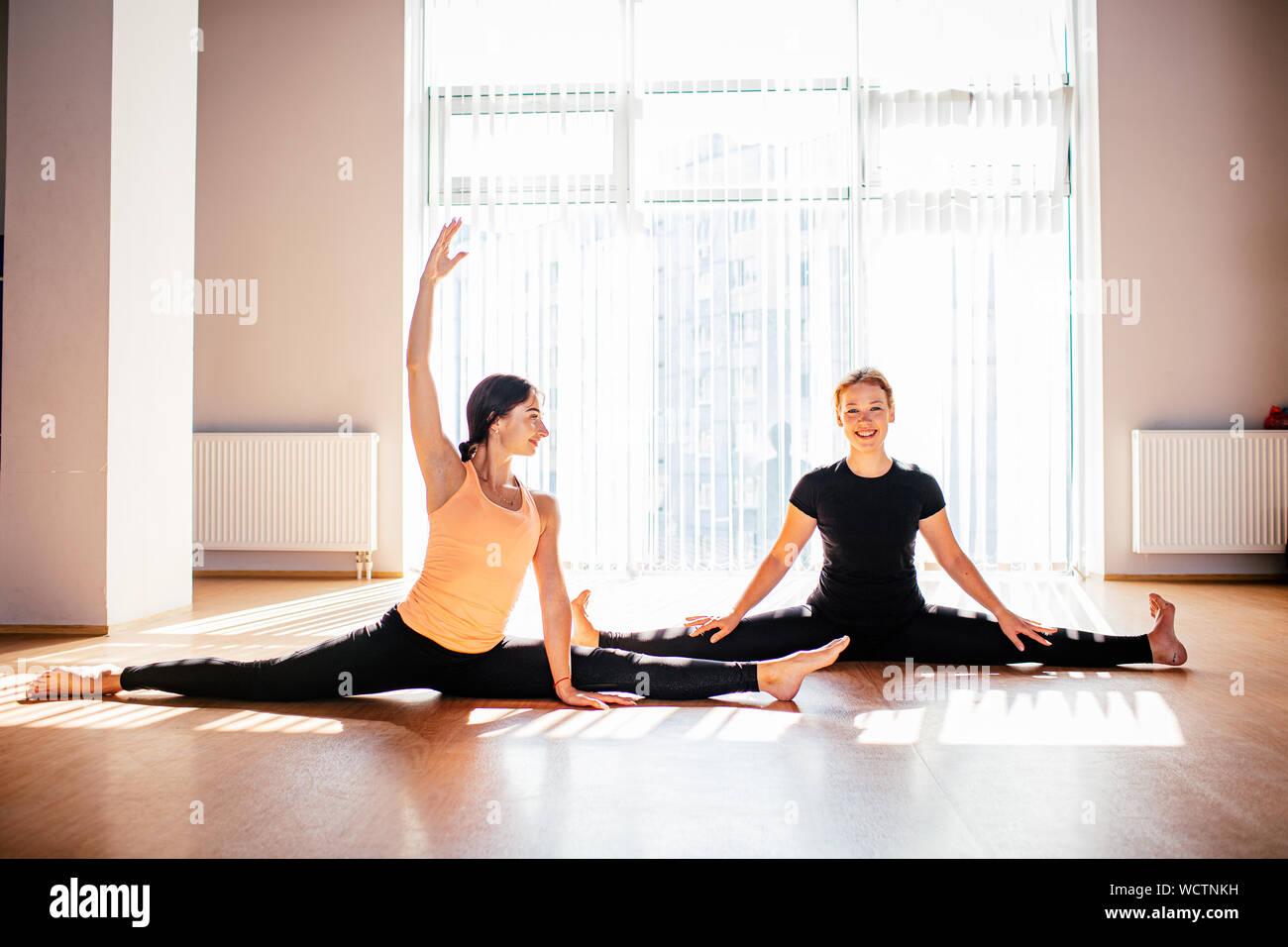 Zwei attraktive junge Frauen balancing und Yoga in einem hellen Studio. Wohlbefinden, Wellness Konzept. Eins der Mädchen ist plus Größe Stockfoto