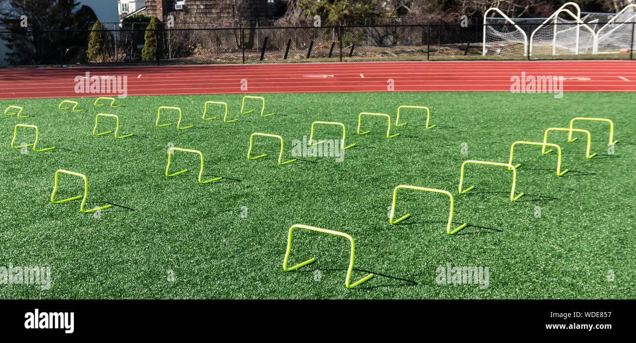 Vorderansicht des Gelben mini Banane Hürden für Geschwindigkeit arbeiten während der Schiene und im Feld der Praxis an einer lokalen High School Track eingestellt. Stockfoto