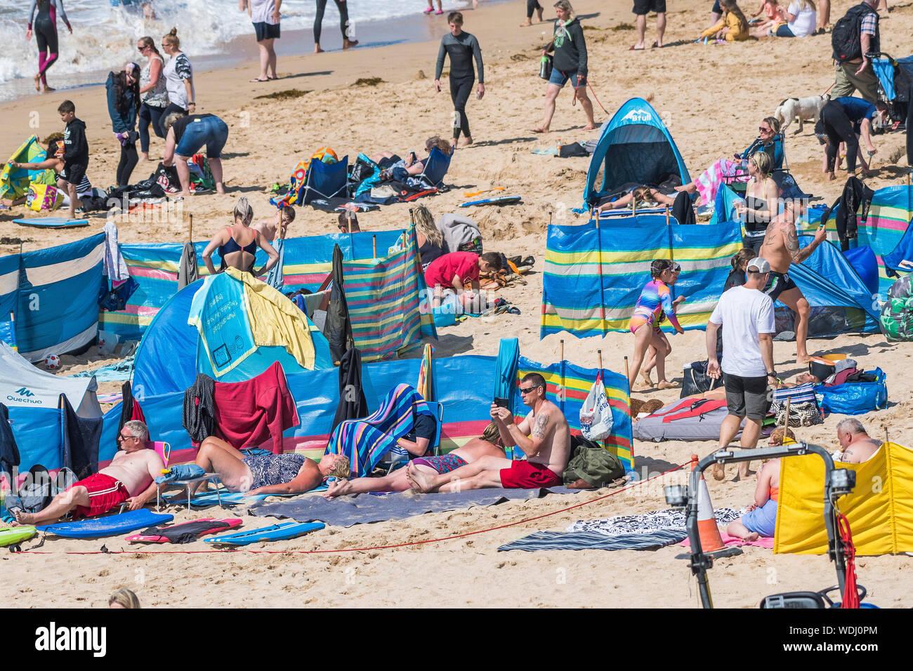 Urlauber genießen selbst auf den Fistral Beach in Newquay in Cornwall im Sommer. Stockfoto