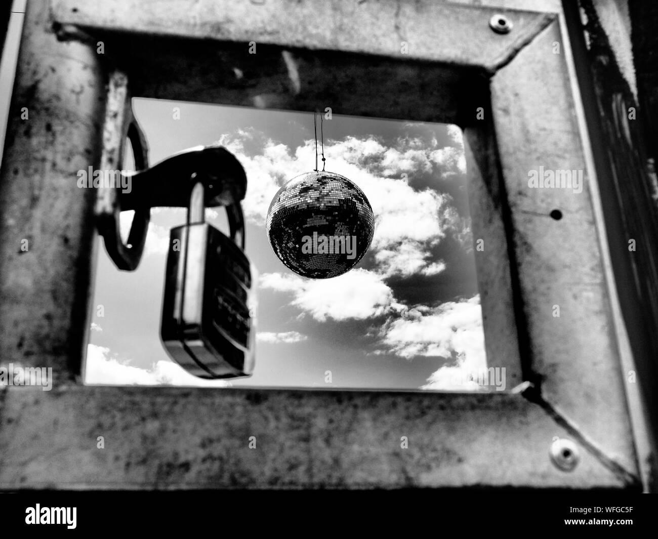 Disco Kugel und Vorhängeschloss gegen Himmel durch das Fenster Stockfoto