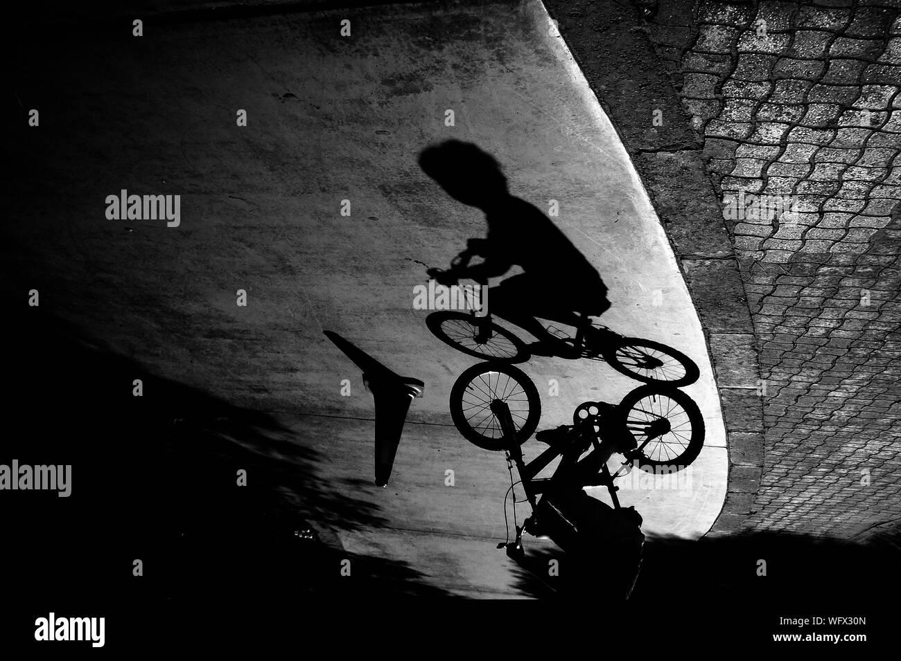 Schatten der Junge Reiten Fahrrad auf der Straße Stockfoto